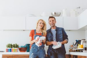 man and woman smiling washing dishes